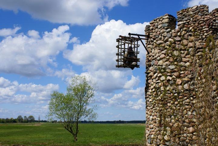 Mittelalterlicher Käfig mit einer Puppe drin an einem Turm vor einer grünen Landschaft